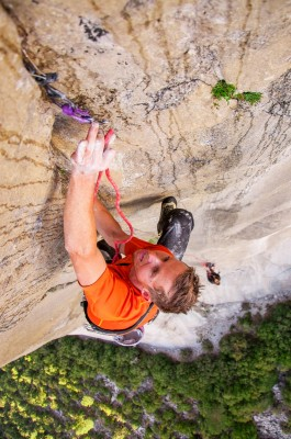 Tommy Caldwell about to thread his rope through a piece of gear placed in a rock crack © Tommyandbecca.blogspot.com